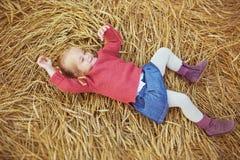 Ładna mała dziewczynka w czerwonej kurtce kłama na ucho banatka Zdjęcie Royalty Free