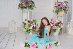 Ładna mała dziewczynka w turkusowej sukni siedzi kwiaty na podłoga i bawić się z Obrazy Stock