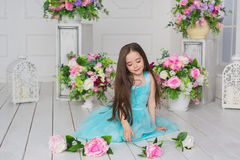 Ładna mała dziewczynka w turkusowej sukni siedzi wśród kwiatów w studiu Obraz Royalty Free