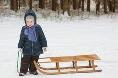 Ładna mała dziewczynka z drewnianym saneczki w zima lesie na mroźnym dniu Zdjęcie Royalty Free