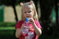 Ładna małej dziewczynki woda pitna obraz stock