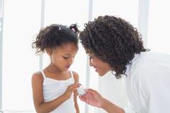 Ładna matka pokazuje ona córki twarzy śmietankę Zdjęcie Stock