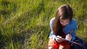 Ładna nastolatek dziewczyna robi nakreśleniom ołówek podczas gdy siedzący w parku Ruch kamera z steadicam zbiory