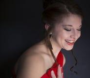 Ładna nastoletnia dziewczyna śmia się czerwoną bal suknię i jest ubranym obraz royalty free