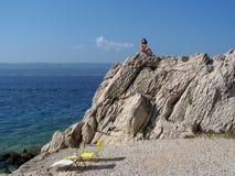 Ładna nastoletnia dziewczyna pozuje na skale na plaży w Chorwacja fotografia royalty free