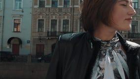 Ładna piosenkarz kobieta wykonuje w starym miasteczku w czarnej skórzanej kurtce zbiory wideo