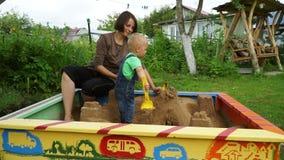 Ładna potomstwo matka z jej małym synem bawić się w piaskownicie Dolly strzał zdjęcie wideo