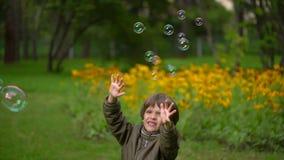 Ładna potomstwo matka z ona bardzo śliczny młody syna cios szczęśliwie gulgocze outdoors w lecie Zwolnione tempo zbiory