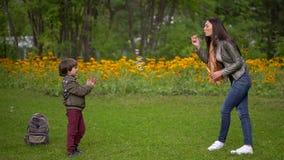 Ładna potomstwo matka z ona bardzo śliczny młody syna cios szczęśliwie gulgocze outdoors w lecie Zwolnione tempo zdjęcie wideo