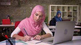Ładna pracująca arabska kobieta w różowym hijab i islamskich ubraniach pisze puszek notatkach i patrzeje jej laptop dokładnie