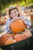 Ładna Preteen dziewczyna Bawić się z Wheelbarrow przy Dyniową łatą Fotografia Royalty Free