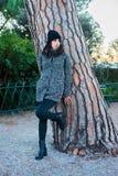 Ładna przyglądająca dziewczyna pozuje obok drzewa w parku obrazy stock