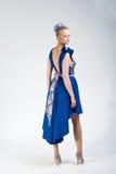 Ładna przyglądająca dziewczyna w jaskrawej sukni z powrotem Obraz Royalty Free