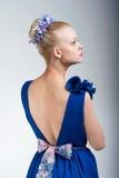 Ładna przyglądająca dziewczyna w jaskrawej sukni z powrotem Obrazy Stock