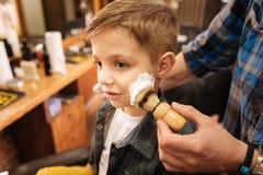 Ładna przyjemna chłopiec ma jego pierwszy golenie Zdjęcia Stock