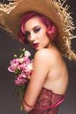 ładna różowa z włosami kędzierzawa dziewczyna w słomianym kapeluszu pozuje z kwiatami przed popielatym zdjęcie royalty free