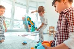 Ładna radosna chłopiec trzyma pudełko z zabawkami fotografia stock