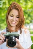 Ładna rudzielec bierze fotografię w parku Fotografia Royalty Free