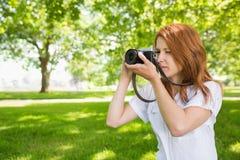 Ładna rudzielec bierze fotografię w parku Obrazy Royalty Free