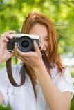 Ładna rudzielec bierze fotografię w parku Zdjęcia Stock