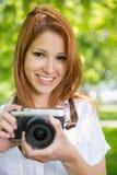 Ładna rudzielec bierze fotografię w parku Fotografia Stock