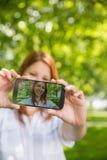 Ładna rudzielec bierze selfie na jej telefonie w parku Zdjęcia Royalty Free
