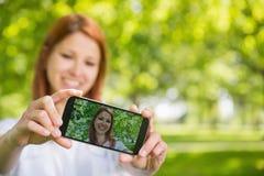 Ładna rudzielec bierze selfie na jej telefonie w parku Obrazy Royalty Free