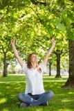 Ładna rudzielec podnosi jej ręki w parku Obrazy Royalty Free
