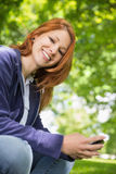 Ładna rudzielec relaksuje w parkowym dosłaniu tekst Obraz Stock