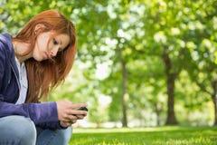 Ładna rudzielec relaksuje w parkowym dosłaniu tekst Zdjęcia Stock