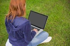 Ładna rudzielec relaksuje w parkowym używa laptopie Obrazy Royalty Free