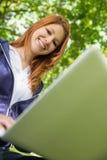 Ładna rudzielec relaksuje w parkowym używa laptopie Obrazy Stock