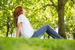 Ładna rudzielec relaksuje w parku Obraz Royalty Free