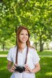 Ładna rudzielec trzyma jej kamerę w parku Zdjęcie Royalty Free