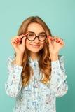 Ładna smiley dziewczyna jest ubranym szkła nad błękitnym tłem Obraz Stock