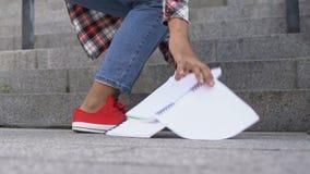 Ładna studencka dziewczyna iść w górę schodków i opuszcza jej notatniki, podnosi one w górę zbiory