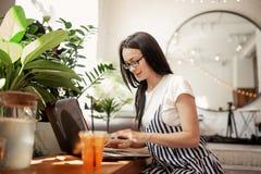Ładna szczupła ciemnowłosa dziewczyna z szkłami, jest ubranym przypadkowego styl, pisać na maszynie coś na jej laptopie w wygodny fotografia royalty free