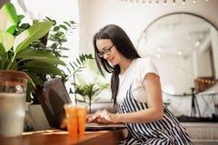 Ładna szczupła ciemnowłosa dziewczyna z szkłami, jest ubranym przypadkowego styl, pisać na maszynie coś na jej laptopie w wygodny obrazy royalty free