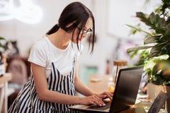 Ładna szczupła ciemnowłosa dziewczyna z szkłami, jest ubranym przypadkowego styl, pisać na maszynie coś na jej laptopie w wygodny obrazy stock