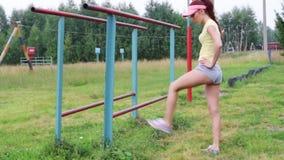 Ładna szczupła dziewczyna w nakrętce robi rozciągania ćwiczeniu przy lata evening plenerowy zdjęcie wideo