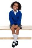 Ładna szkolna dziewczyna sadzająca swobodnie na ławce Obraz Royalty Free
