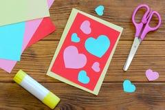 Ładna walentynka dnia karta z papierowymi sercami, nożyce, kleidło kij, barwiący papier ciąć na arkusze na drewnianym tle Zdjęcia Royalty Free