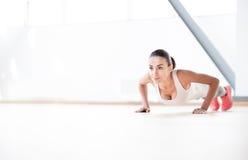 Ładna wytrwała kobieta robi fizycznemu ćwiczeniu Zdjęcie Stock