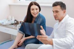 Ładna zadowolona lekarka pokazuje X promienia fotografię zdjęcie stock