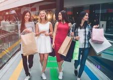 Ładne dziewczyny chodzą wpólnie w centrum handlowym Robią zakupy Młode kobiety torby w ich rękach dziewczyny się śmiać fotografia stock