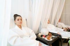 Ładne dziewczyny relaksuje w karłach w bathrobes obrazy stock