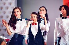 Ładne kobiety ma zabawę na karaoke przyjęciu obraz stock