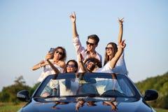 Ładne młode dziewczyny i faceci w okularach przeciwsłonecznych siedzą w czarnym kabriolecie na drogowym mieniu ręki w górę robić  fotografia royalty free