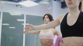 Ładne yogini kobiety robią ćwiczeniom w sprawności fizycznej studiu zdjęcie wideo