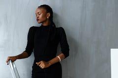 Ładnego afrykanina lub czarnej amerykańskiej kobiety trwanie przymknięcie ono przygląda się na zmroku - szary pracowniany tło Obraz Royalty Free